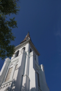 A traditional white church steeple rising into a clear blue sky in Charleston, South Carolina